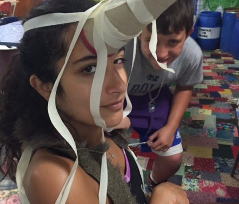 A girl with a paper towel roll taped to her head, a smiling boy is hiding behind her.
