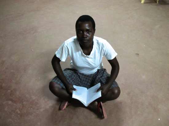 Student sits on floor reading book