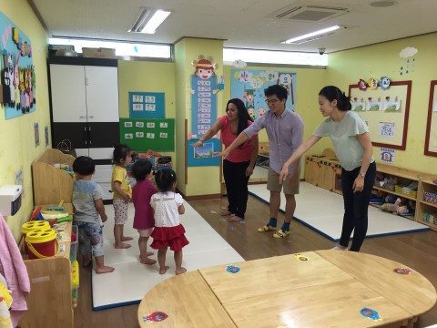 Three people in a classroom instructing small children