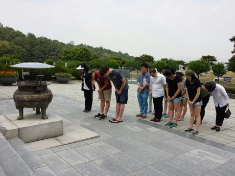 Group of students bowing their heads outdoors.