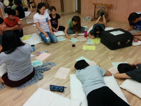 Group of people seated on floor writing on pieces of paper.