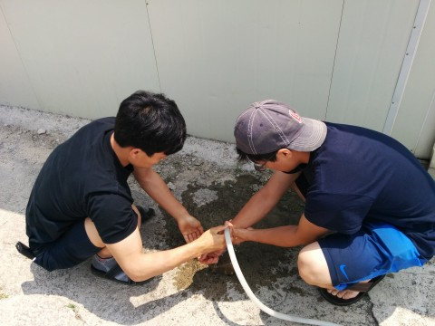Two people kneeling at a hose outdoors.