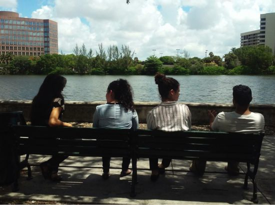 Students sitting on a bench by a river