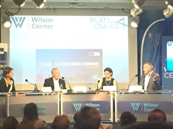 Panel of two men and two women speaking a the Wilson Center with a screen in the background