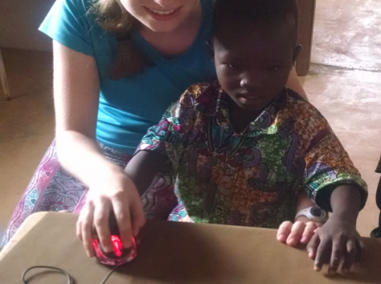Woman helps young child use a computer
