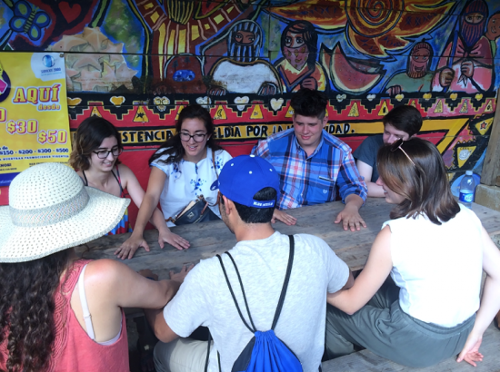 Students seated at a picnic table play a game