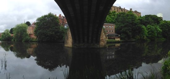 Reflective body of water under a bridge