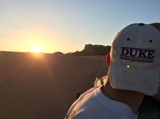 "Student wearing hat reading ""Duke University"" looks at sunset"