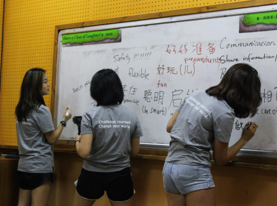 Group of students write phrases on a white board