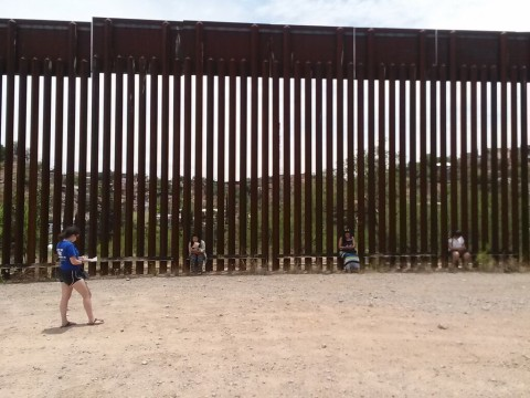 Woman standing in front of border wall