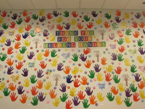 "Wall decorated with handprint cutouts and sing that reads ""Thank You For Your Helping Hands!"""