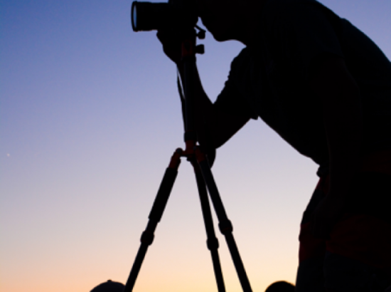 Silhouette of person taking photo with camera on tripod