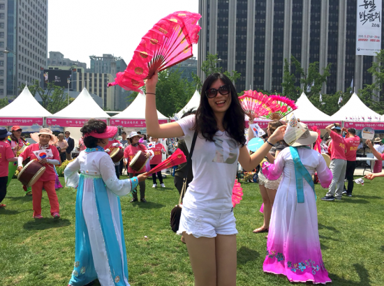 Woman holds a pink fan outdoors