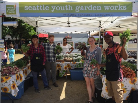 "Students hold up carrots at an outdoor produce market under sign that reads ""seattle youth garden works"""