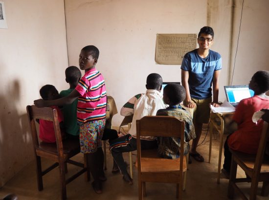 A young adult working with children on computers