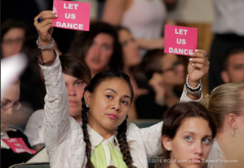 "A woman hold two ""Let Us Dance"" signs at a city hall meeting in New Orleans"