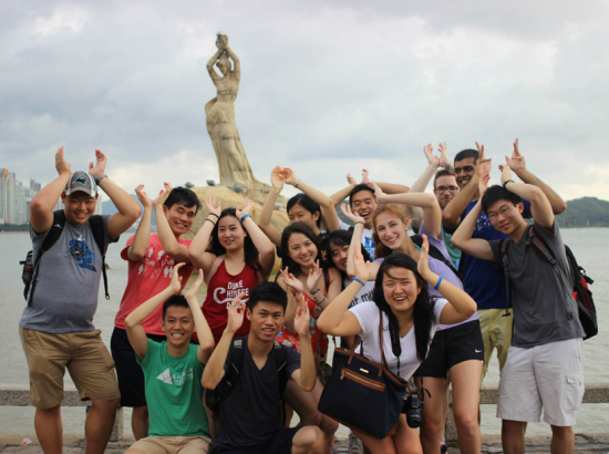 Group of students with arms in the air in front of body of water