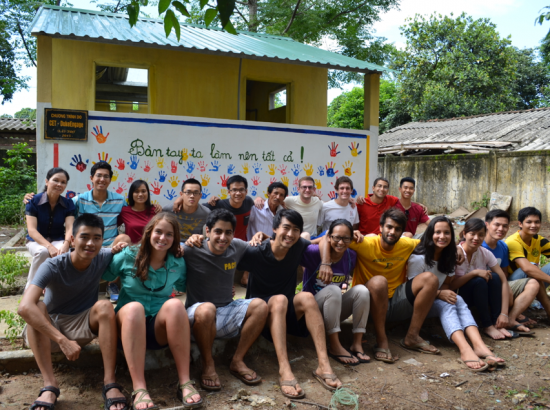 Students seated with arms around each other outdoors in front of a small building