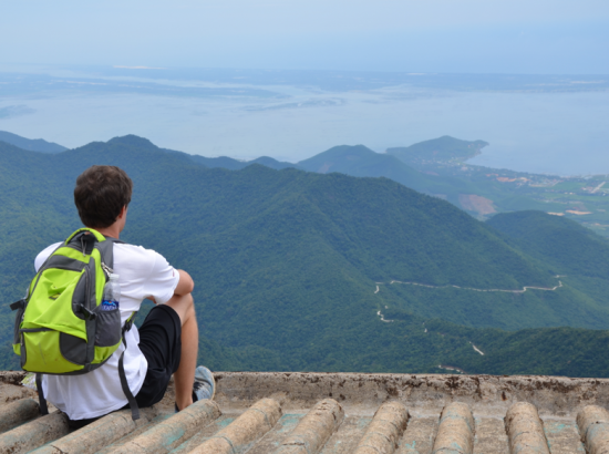 Student seated overlooking mountains in distance