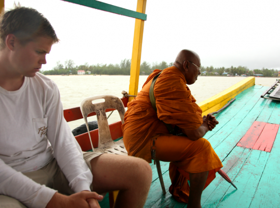 Two men seated on a colorful wooden boat