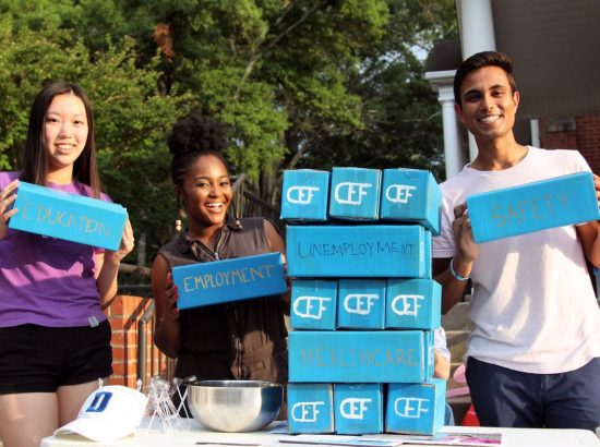 three young people holding blocks with finance-related words