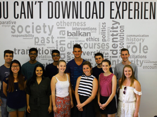 group of young people standing in front of a wall of inspiring words