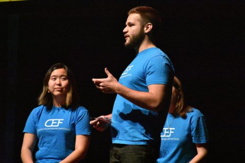 three speakers on stage wearing blue t-shirts