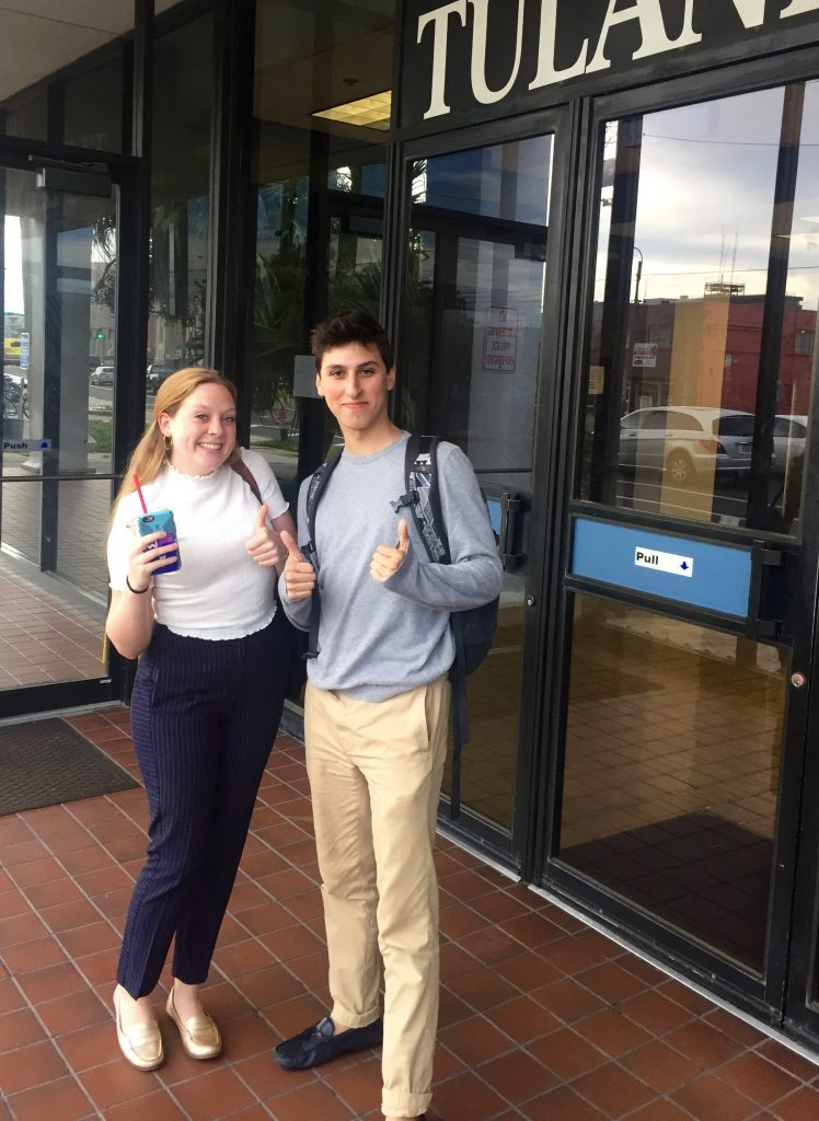 two young people outside a business