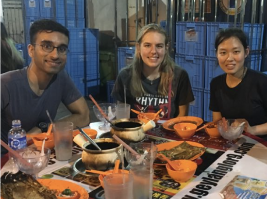 young people sitting around a table filled with food
