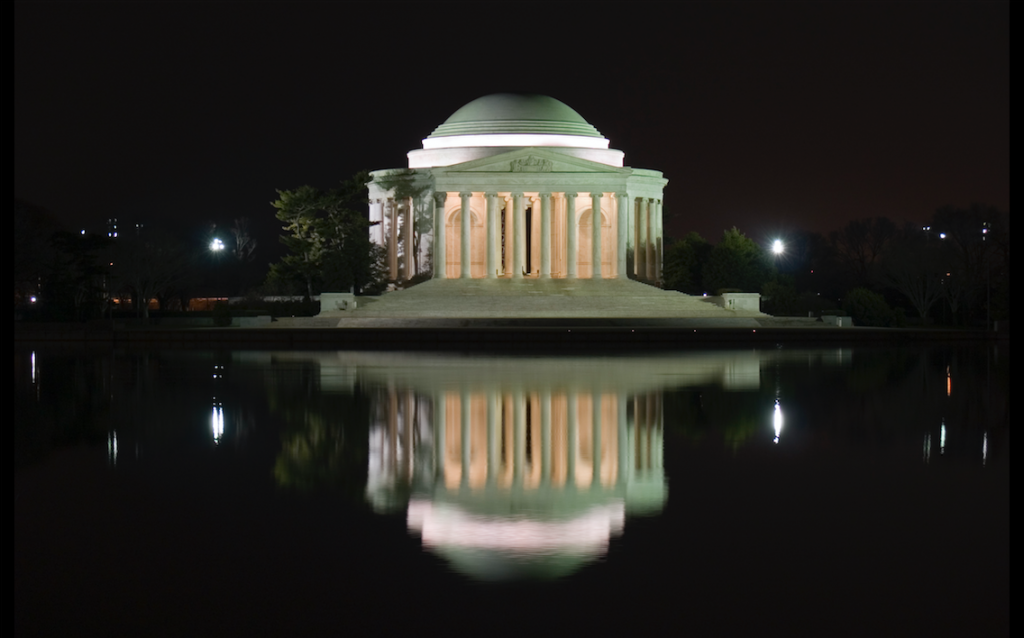White marble building in front of a body of water