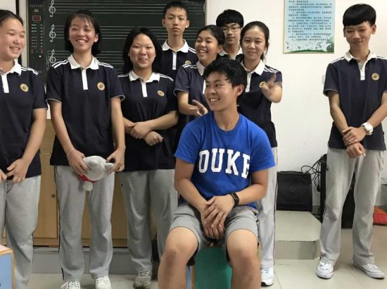 duke student surrounded by Chinese school children