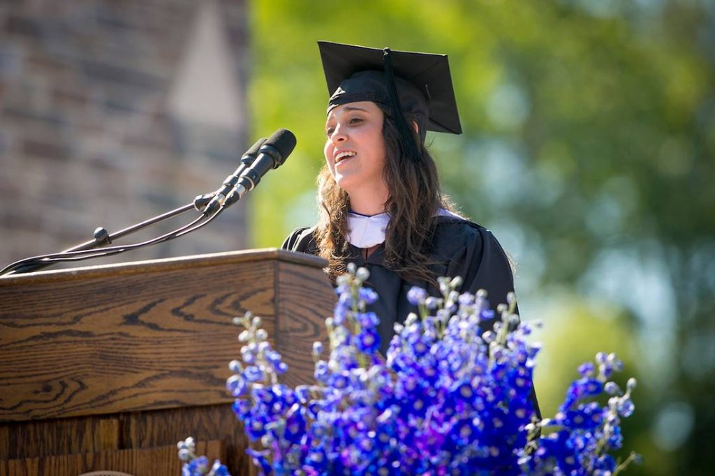 young woman in graduation gown at podium