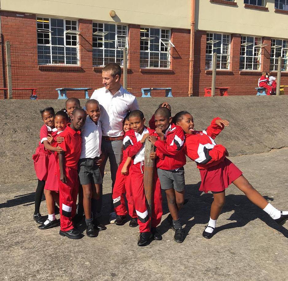 young man surrounding by school children