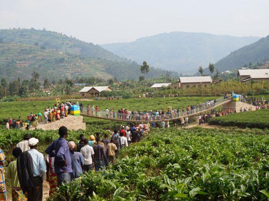 communities in Rwanda gather and walk across a bridge