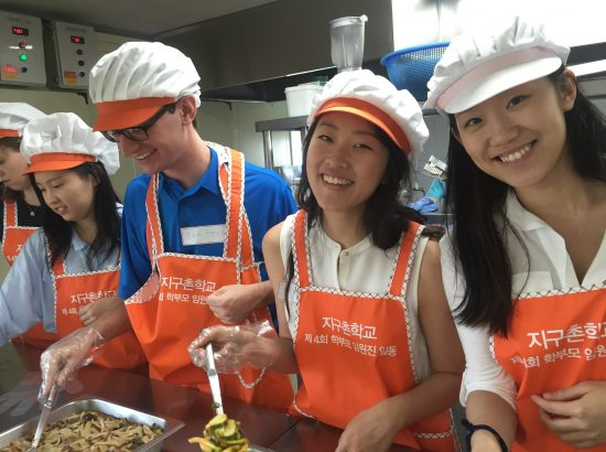 four students adorned with bright orange aprons and caps serve lunch food while smiling at the camera