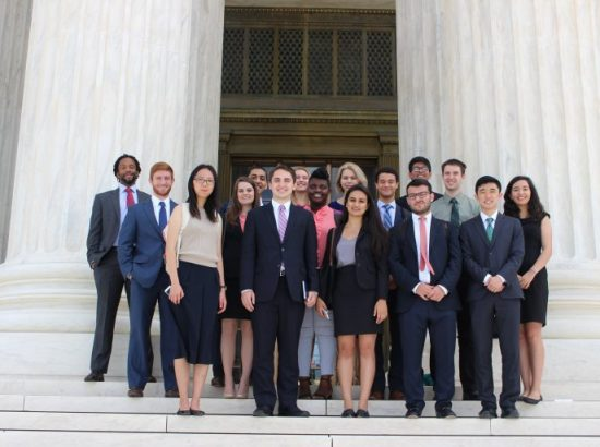 group of young people in professional clothing standing on the front steps of a marble building