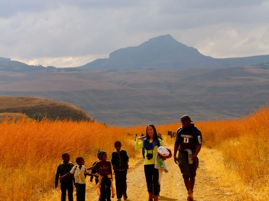 two adults and four young children walking along a dusty road, mountains in background