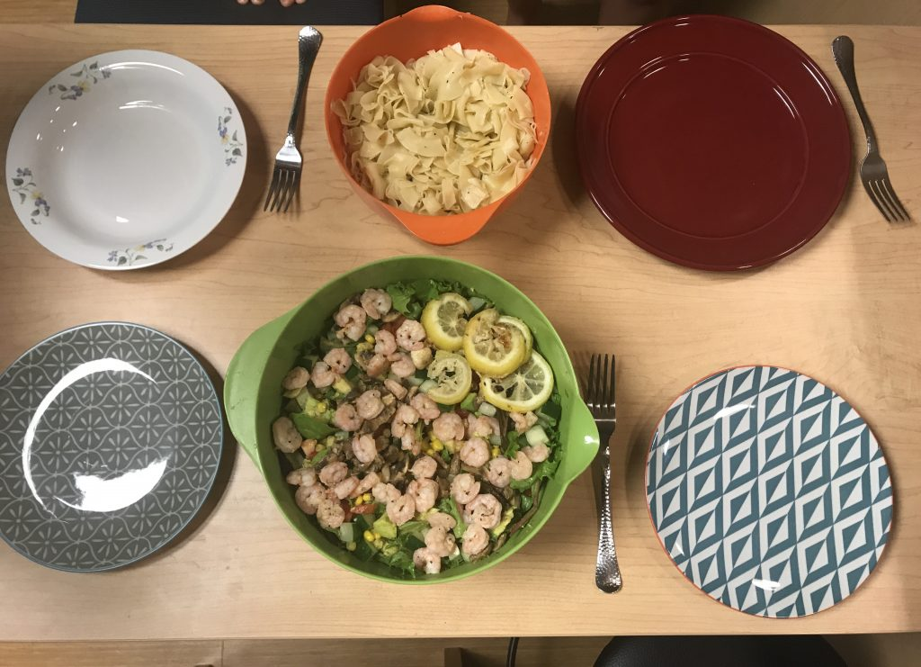 four empty dinner plates and two serving dishes on a table