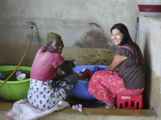 A community member and a DukeEngage student washing dishes in basins