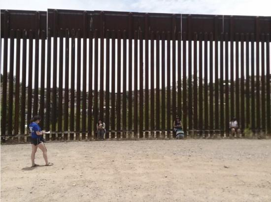 DukeEngage students sitting on the border wall