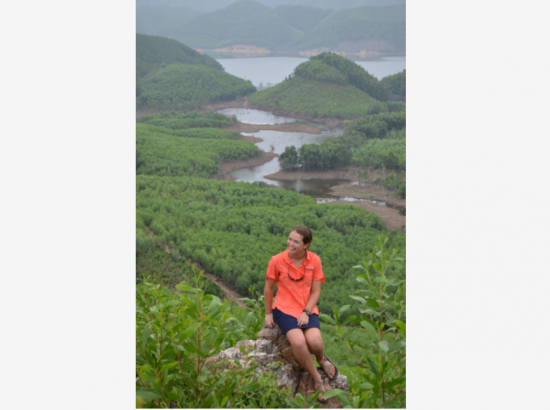 DukeEngage student sits on a rock in front of a river in Vietnam