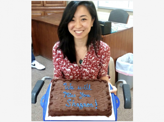 """DukeEngage student holds chocolate cake that reads """"We will miss you Shannon!"""""""