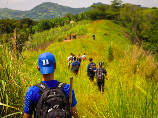 DukeEngage student follows others across a grassy plain