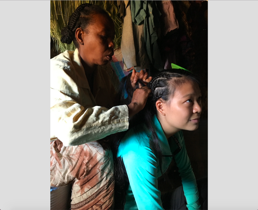 a Malagasy woman braids Kelly's hair into rows