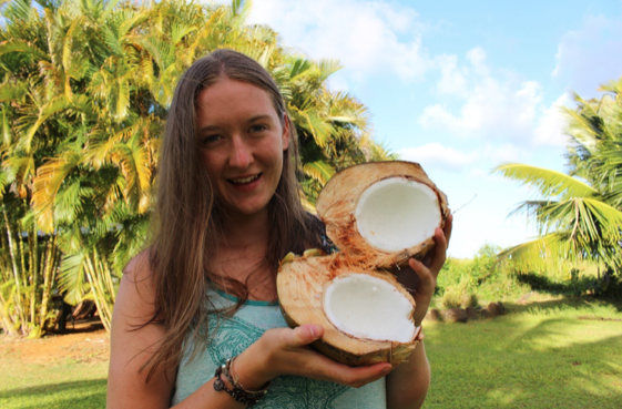 young woman with two halves of an open coconut