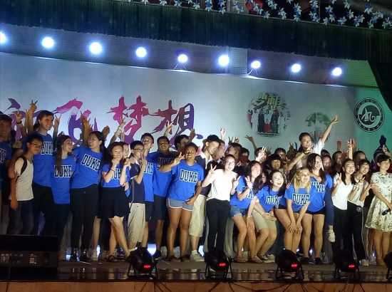large group of performers dancing on stage wearing duke tshirts