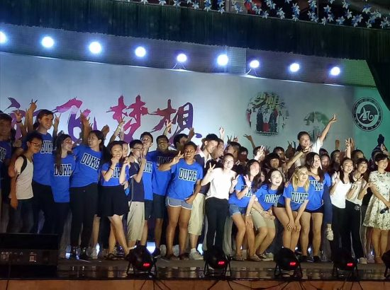 25-30 young people on stage, waving