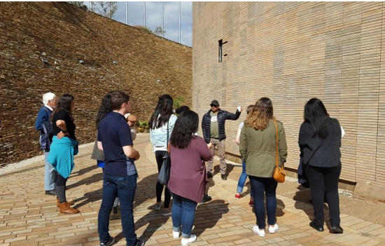 group of people looking at wall with words inscribed
