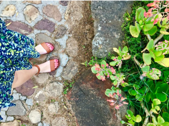 student's feet amid her walk through the gardens