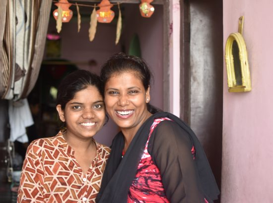 two women smiling and posing for the camera